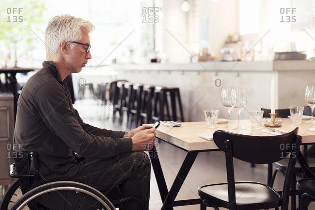 Man on wheel chair, using smartphone in restaurant