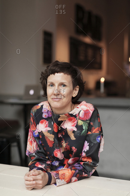 Mature woman sitting by table, looking at camera