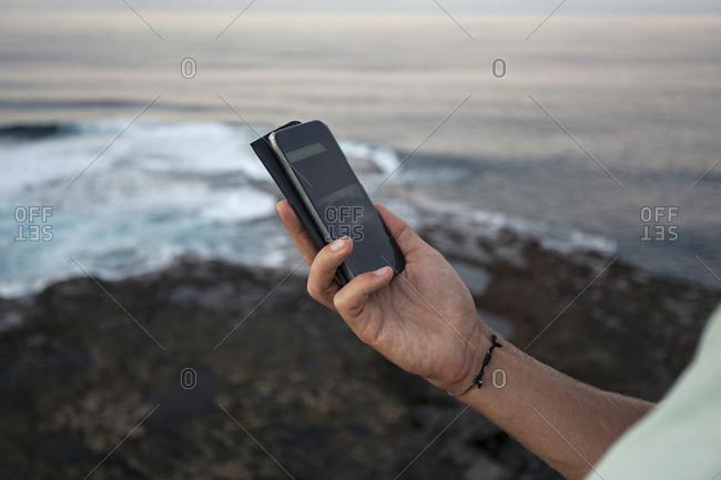 Man holding cell phone near sea coast