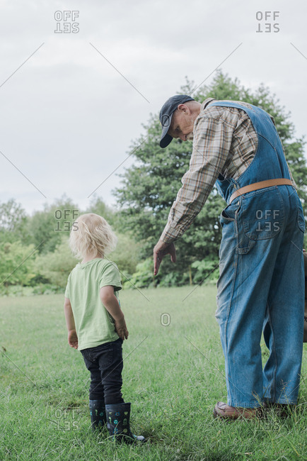 Grandparent with grandson in meadow