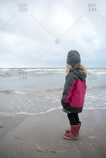 Girl on beach looking at sea