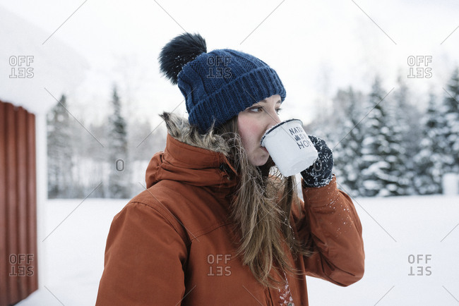 Young woman drinking coffee while hiking in winter