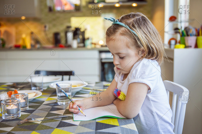 Girl drawing in kitchen