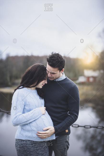 Man embracing pregnant woman outdoors