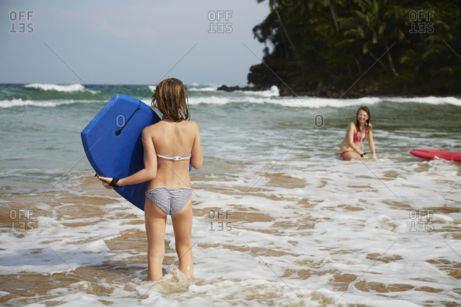 Girls with swimming boards in sea