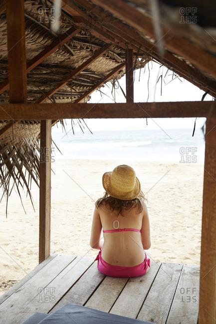 Girl sitting on table on beach
