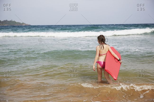 Girl with swimming board in sea