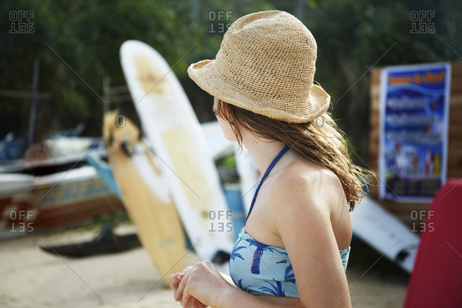 Girl standing next to surfboards