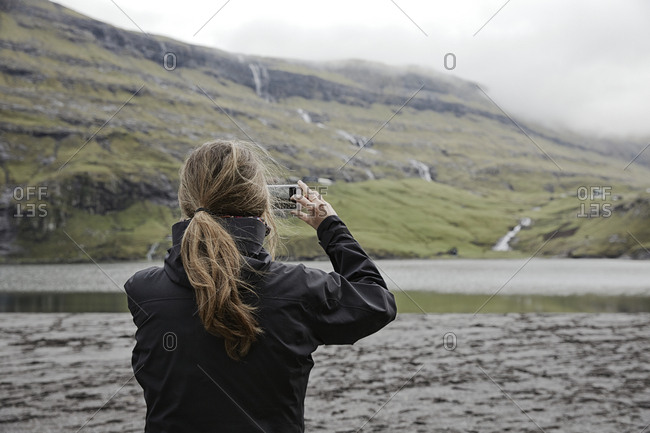 Woman photographing lake