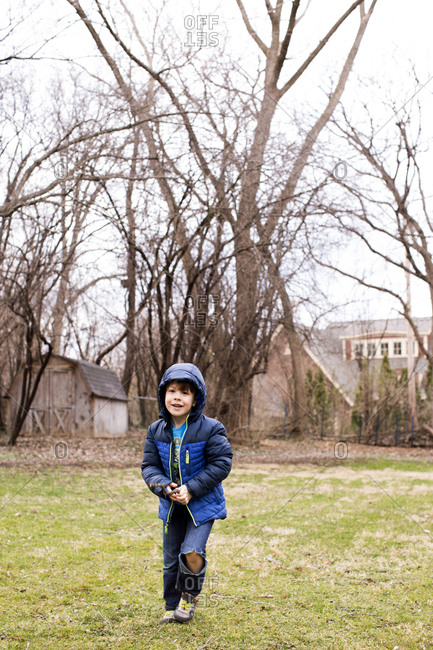 Young boy smiling outdoor, in a yard in the wintertime