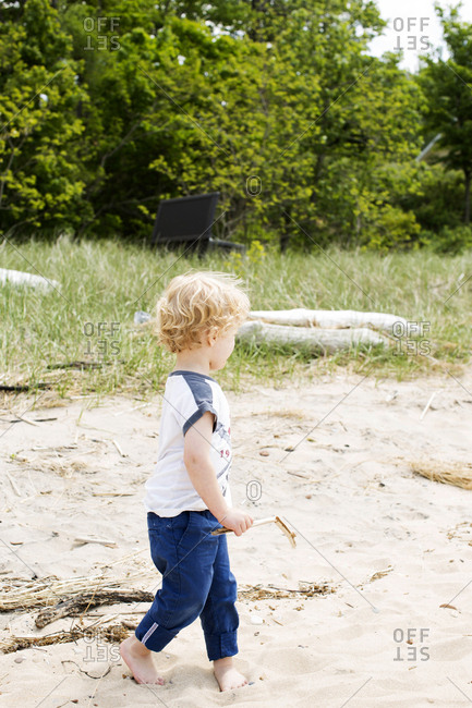 Profile of a toddler walking on the beach holding a stick