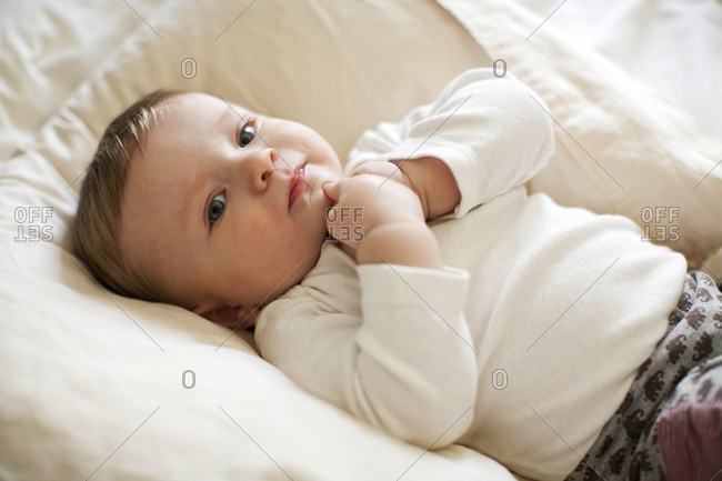 Adorable baby laying down, touching his chin