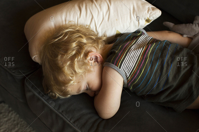 Blonde toddler asleep on a couch