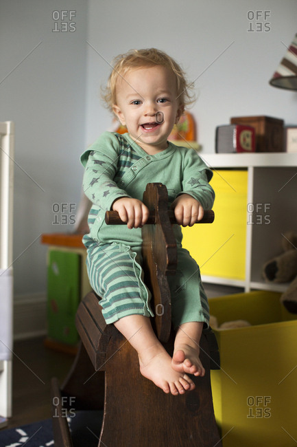Happy toddler on a wooden rocking horse in his bedroom