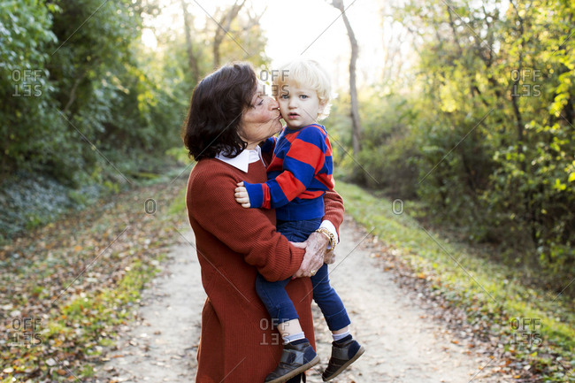 Portrait of a woman kissing her grandson's cheek on an outdoor path
