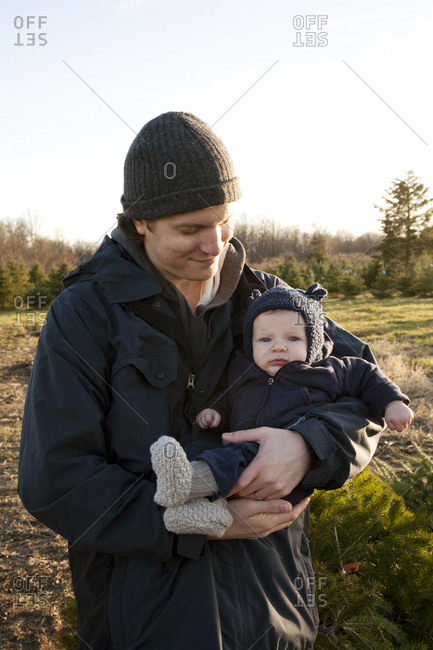 A father and his infant son at a Christmas tree farm