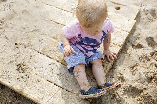Overhead view of a toddler sitting on a wood plank in the sand