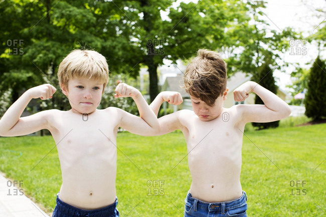 Two kids flexing their muscles outside