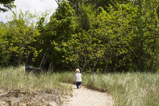 Toddler walking towards a staircase, away from the beach