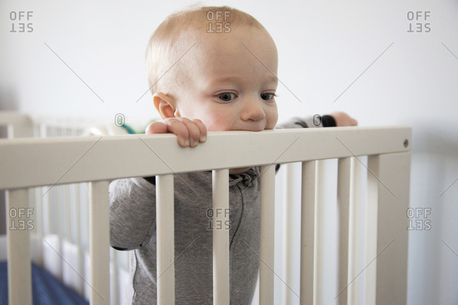 Baby standing up chewing on his crib rail
