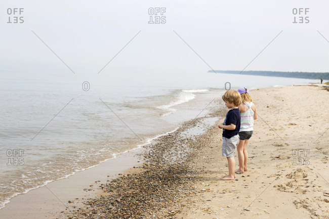 Two young friends standing on the beach looking at a lake