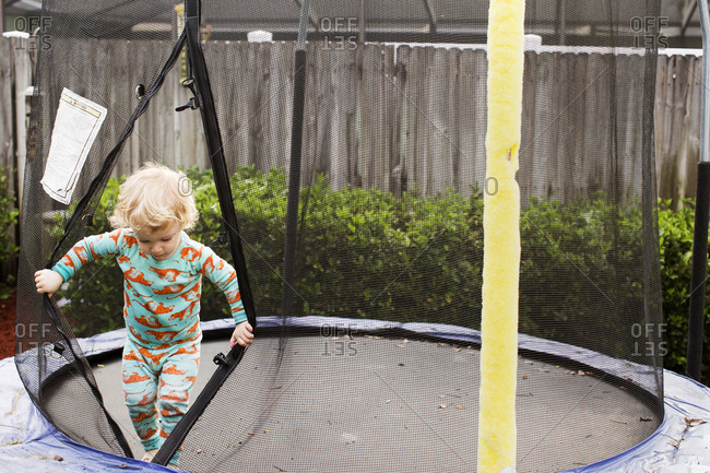 Toddler climbing out of a trampoline enclosure