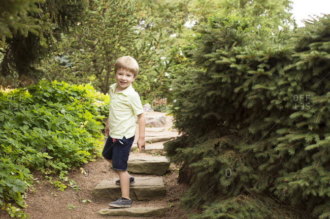 Young boy, outside, smiling on a stone path between trees