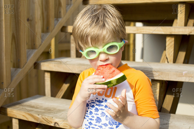 Little boy eating watermelon with goggles on outside