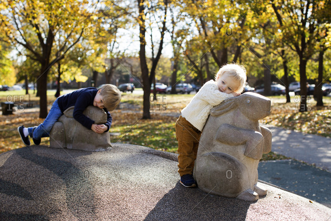 Two young brothers relaxing on animal sculptures in a park during fall
