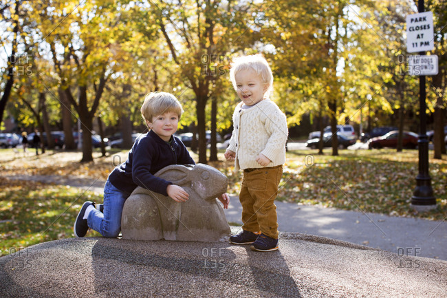 Portrait of two young brothers sitting on an animal sculpture in a park during fall