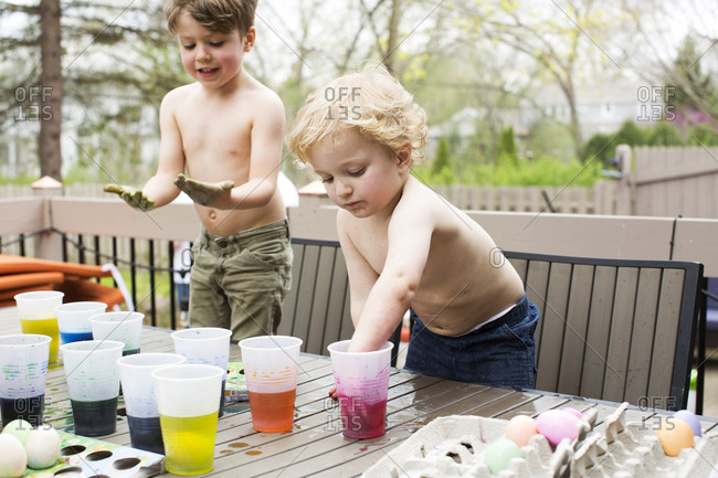 Young friends coloring eggs on a table outside