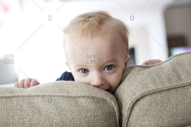 Portrait of a blonde baby peeking over a couch