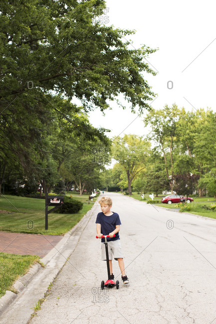 Young boy riding his scooter on a suburban street