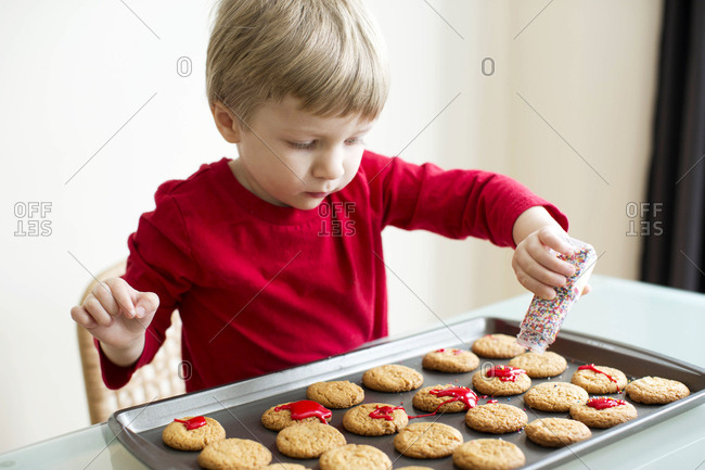 Little boy decorating cookies with sprinkles and icing