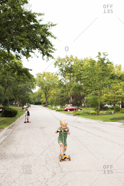 Two young brothers riding scooters on a suburban street