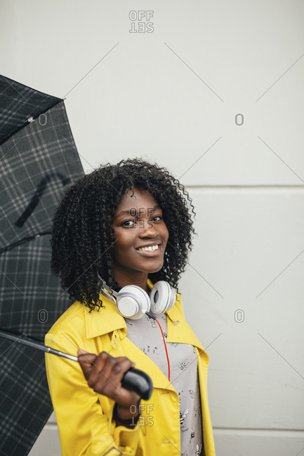 Portrait of young black woman holding umbrella and smiling to camera
