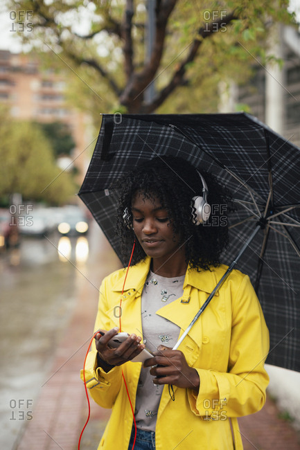 Young black woman listening to music on smartphone while waiting on side of street holding umbrella