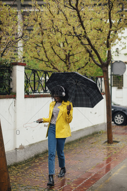 Young black woman enjoying music walking down the street in the rain