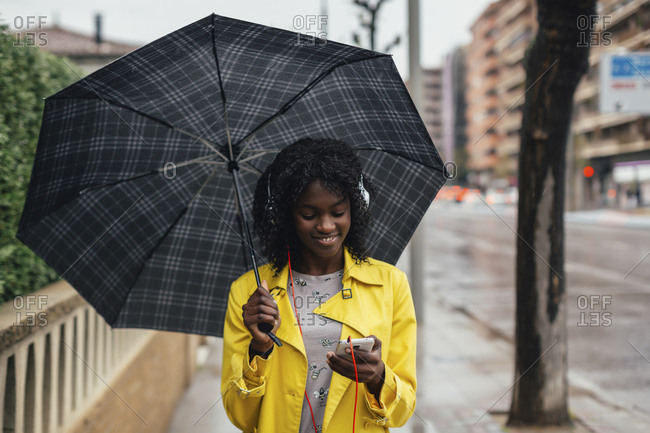 Young black woman checking her messages and smiling walking down the street in the rain