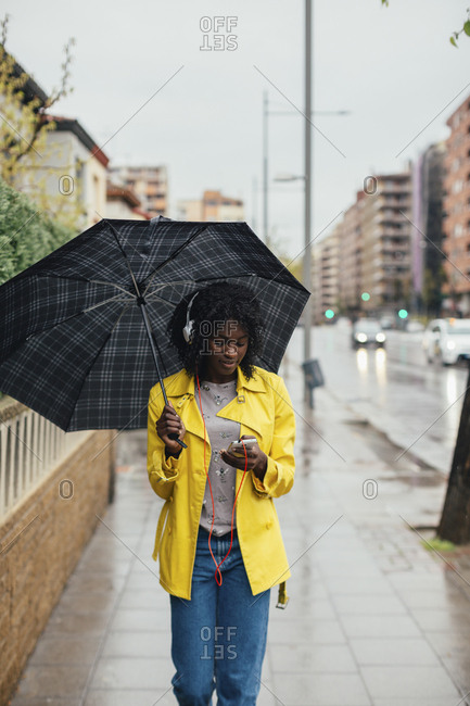Young black woman looking down at phone while walking down the street in the rain