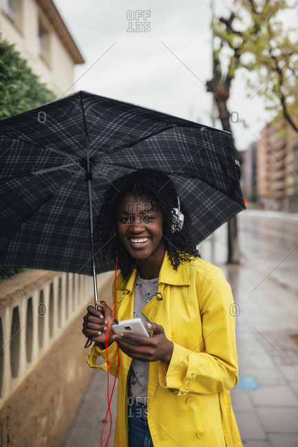 Young radiant woman laughing listening to music on smartphone standing on the street in the rain