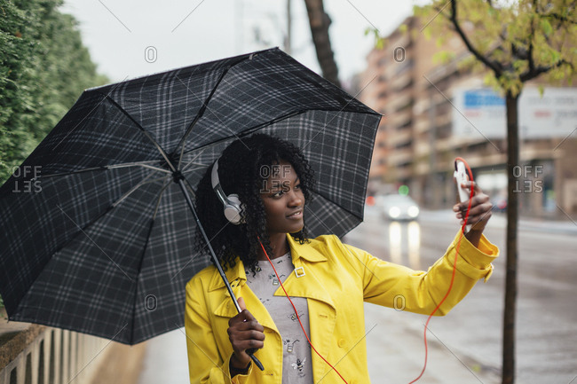 Young woman taking selfie with smartphone on the street holding umbrella