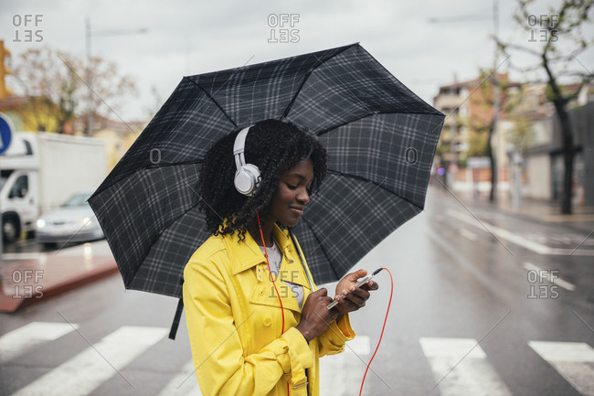 Young black woman looking down at phone while crossing the street in the rain