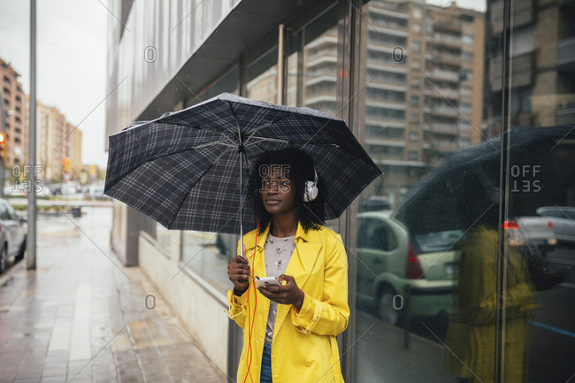 Young black woman waiting in the rain on the street while listening to music on smartphone