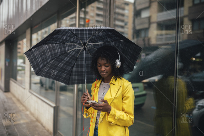 Young woman looking down at smartphone while waiting on the street in the rain