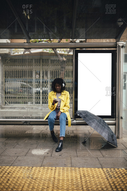 Young black woman looking down at smartphone while waiting for a bus in the rain