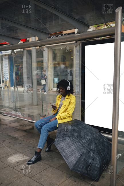 Young woman sitting in bus shelter checking her smartphone with umbrella open next to her
