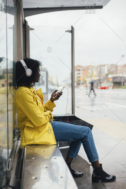 Side view of young black woman listening to music on smartphone while waiting in bus shelter