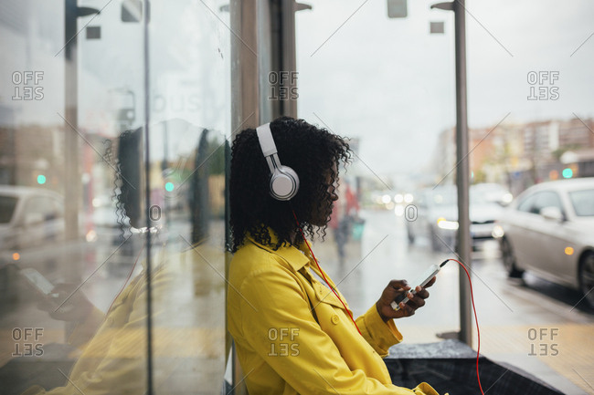 Profile view of young woman sitting in bus shelter checking smartphone on gloomy day