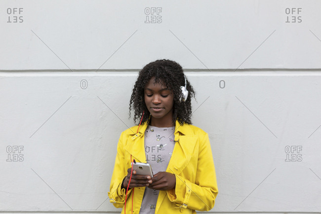 Portrait of young black woman standing against wall looking down at phone